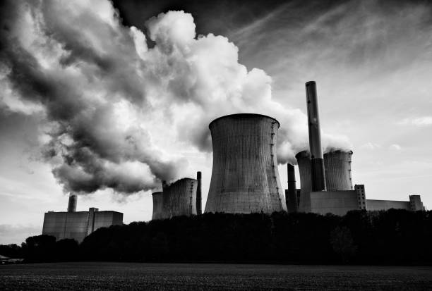 Black and white photograph of a coal fired power plant with pollution stock photo