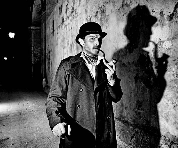 Black and white picture of a detective smoking his pipe Man dressed up as famous detective Sherlock Holmes outdoors, including typical shadow  Note: All props in this shoot including pipe are authentic vintage items. Slight light trails and motion blur on arms. Black and White. Grain Added.  [url=file_closeup.php?id=13571687][img]file_thumbview_approve.php?size=1&id=13571687[/img][/url] [url=file_closeup.php?id=13548314][img]file_thumbview_approve.php?size=1&id=13548314[/img][/url] [url=file_closeup.php?id=13548292][img]file_thumbview_approve.php?size=1&id=13548292[/img][/url] [url=file_closeup.php?id=13548271][img]file_thumbview_approve.php?size=1&id=13548271[/img][/url] [url=file_closeup.php?id=13548249][img]file_thumbview_approve.php?size=1&id=13548249[/img][/url] [url=file_closeup.php?id=13548231][img]file_thumbview_approve.php?size=1&id=13548231[/img][/url] [url=file_closeup.php?id=13894179][img]file_thumbview_approve.php?size=1&id=13894179[/img][/url] [url=file_closeup.php?id=13894166][img]file_thumbview_approve.php?size=1&id=13894166[/img][/url] sherlock holmes stock pictures, royalty-free photos & images