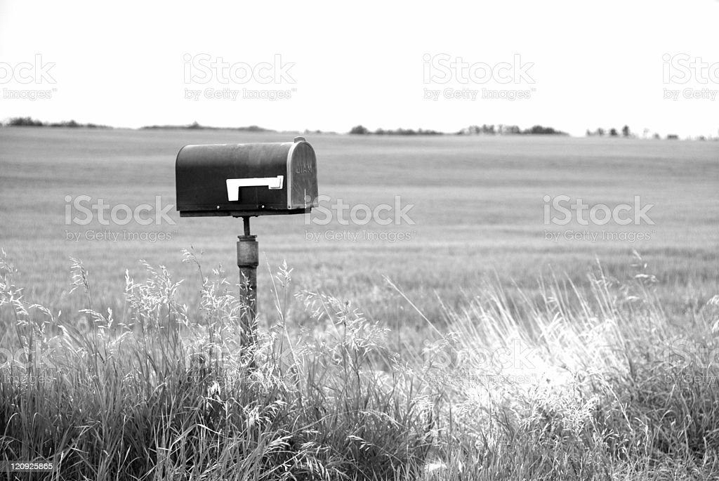 Black and white picture of a mailbox surrounded by fields stock photo