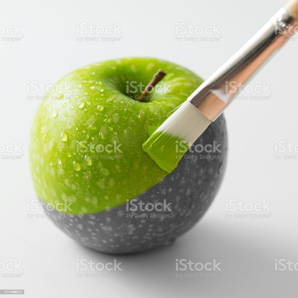A black and white picture of an apple being painted green stock photo