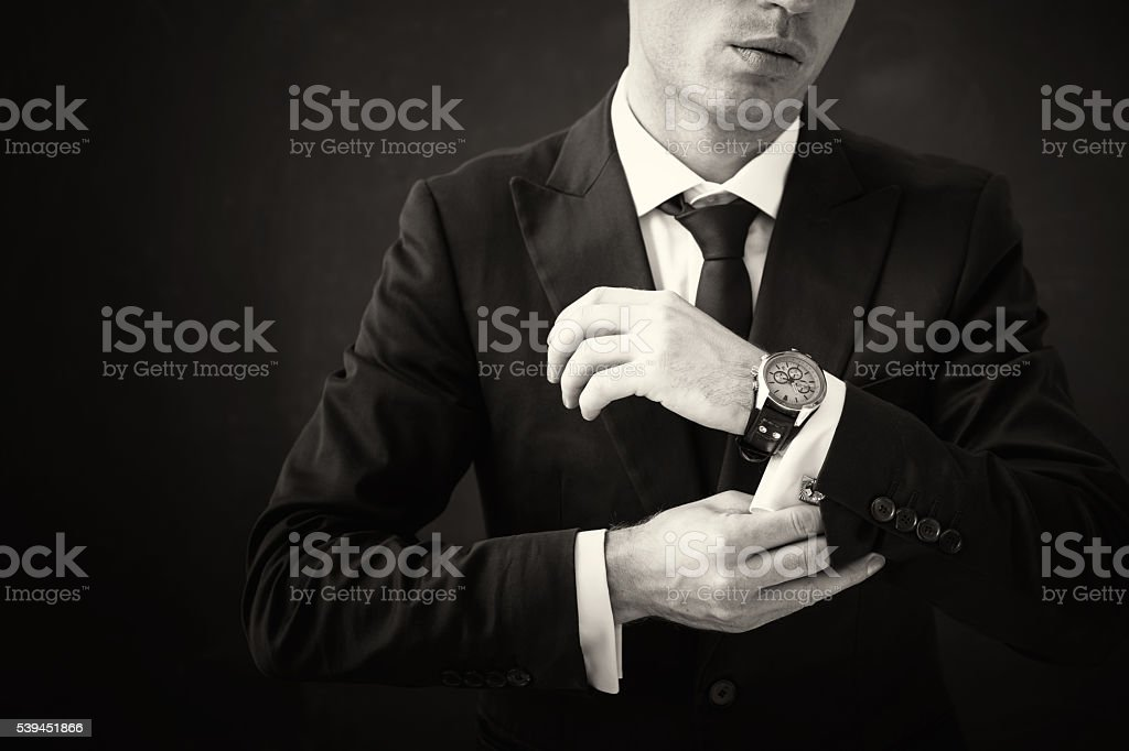 Black and white picture of business man fixing his shirt stock photo