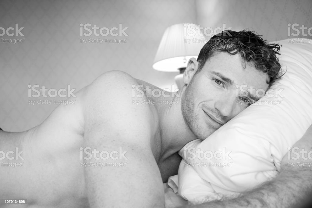 Black and white picture of handsome naked man lying on hotel room bed sheets stock photo