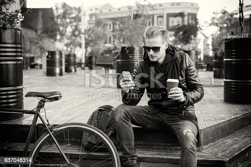 istock Black and white picture of man having coffee and using smartphone 637048314