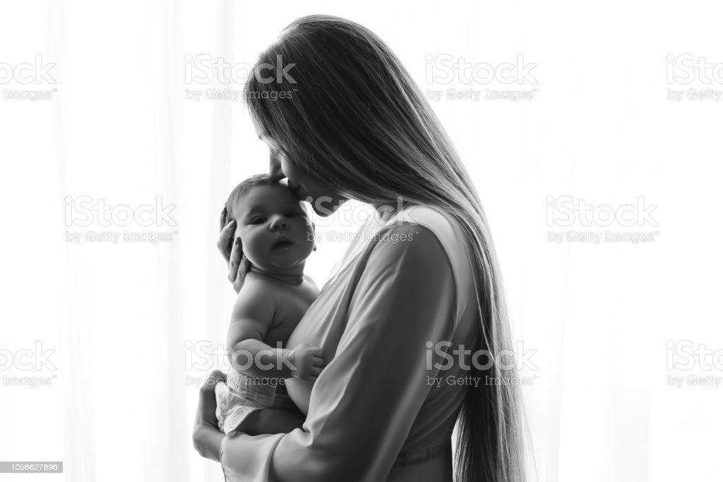 photo noir et blanc de mère embrassant le petit garçon de bébé en face de rideaux à la maison photo libre de droits