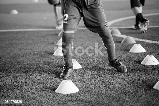 black and white picture of soccer player Jogging and jump between cone markers on artificial turf for soccer training. Football or Soccer Academy.