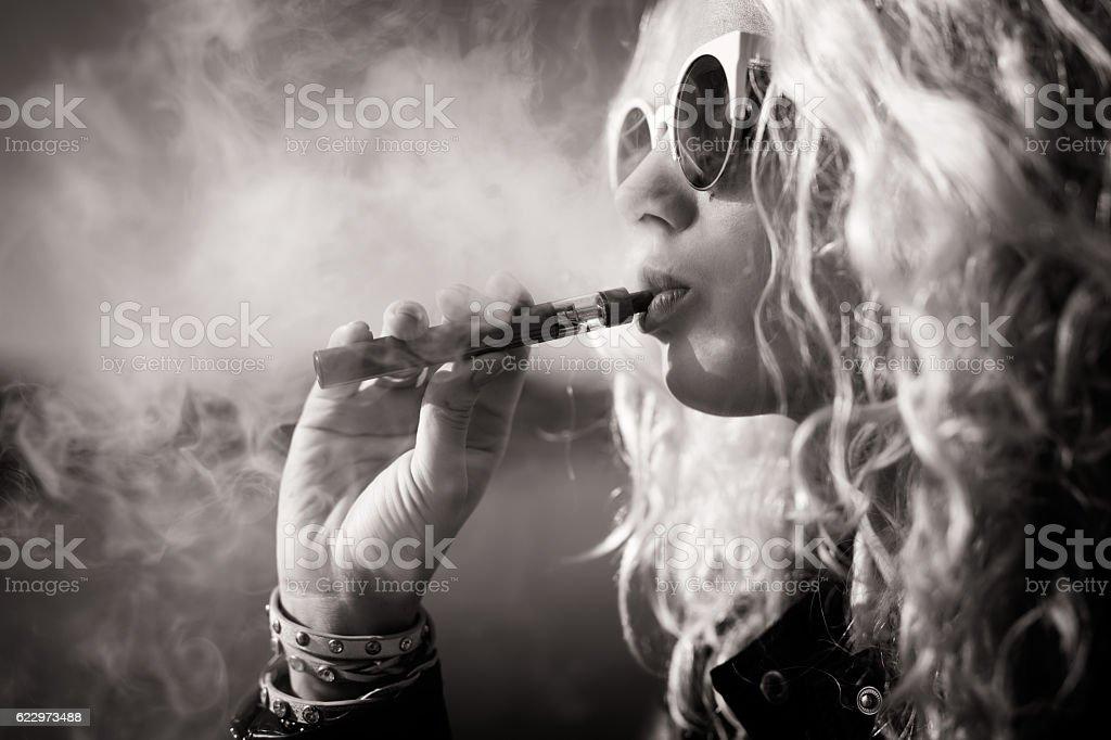 Black and white picture of woman smoking e-cigarette stock photo