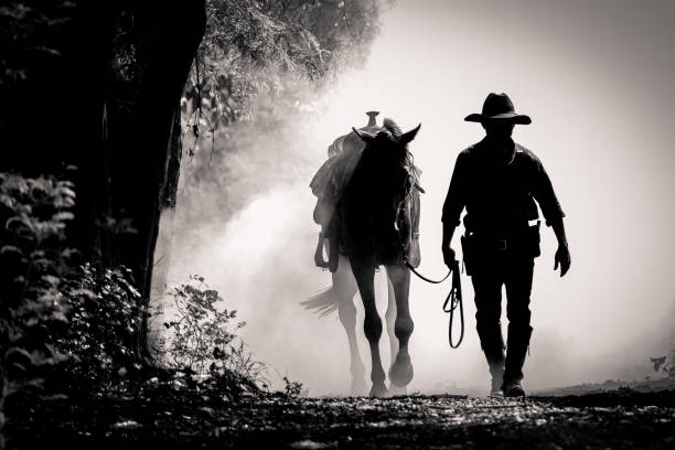 black and white picture silhouette of the cowboy and the horse in the morning sunrise