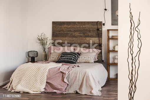 Black and white pillow on pastel pink and beige bedding