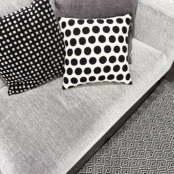 schwarz und weiß gepunktet kissen auf sofa - teppich geometrisch stock-fotos und bilder