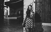 Black and white portrait of a young fashionable brunette walking and relaxing in the old town of Rovigno, Istria, Croatia. She is just outside her apartment in the Old town, wearing a striped summer dress. Shot in letterbox aspect ratio for more horizontal copy space.