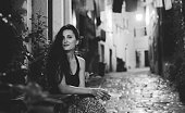 Black and white portrait of a young fashionable brunette relaxing in the old town of Rovigno, Istria, Croatia. She is just outside her apartment in the Old town, enjoying the quiet summertime evening in town. Shot in letterbox aspect ratio for more horizontal copy space.
