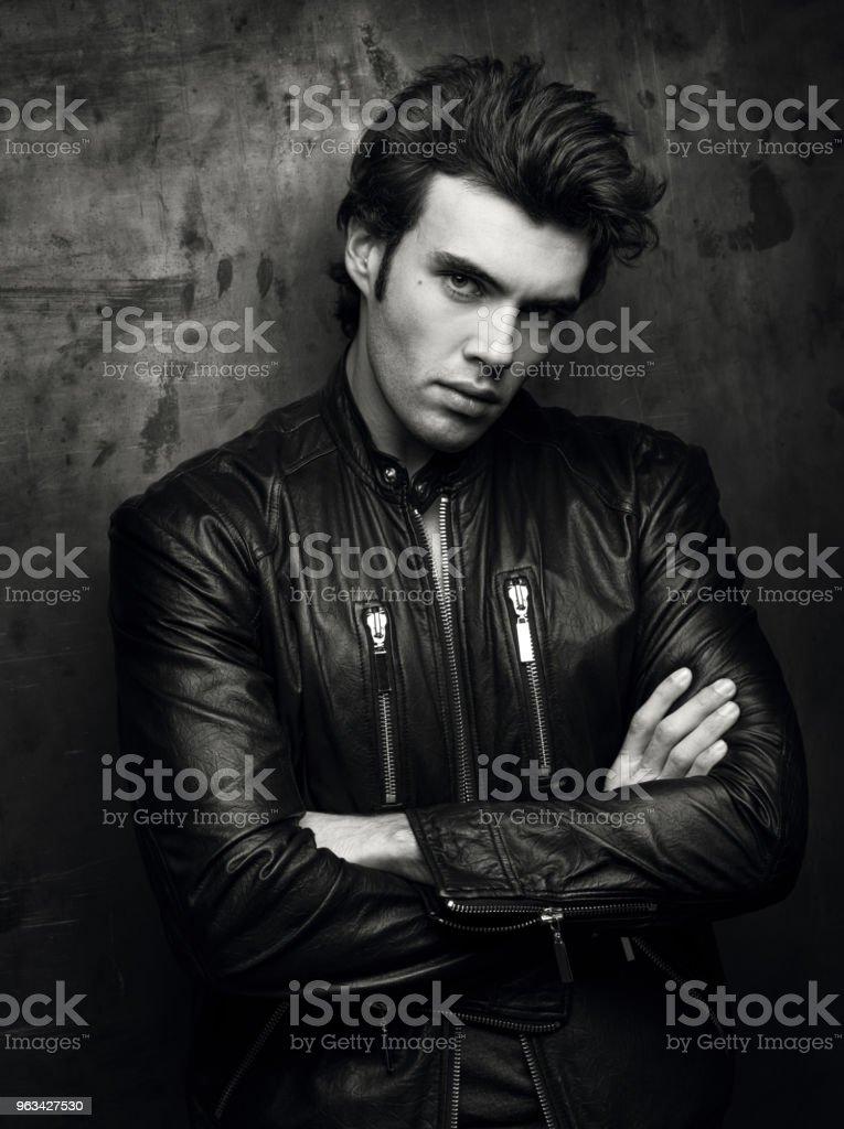 Black and white portrait of a man in a black leather jacket near wall - Zbiór zdjęć royalty-free (Codzienne ubranie)
