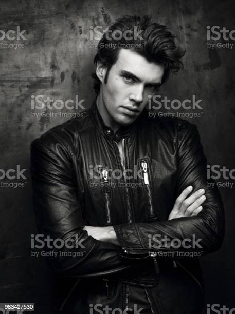 Czarnobiały Portret Mężczyzny W Czarnej Skórzanej Kurtce W Pobliżu Ściany - zdjęcia stockowe i więcej obrazów Codzienne ubranie
