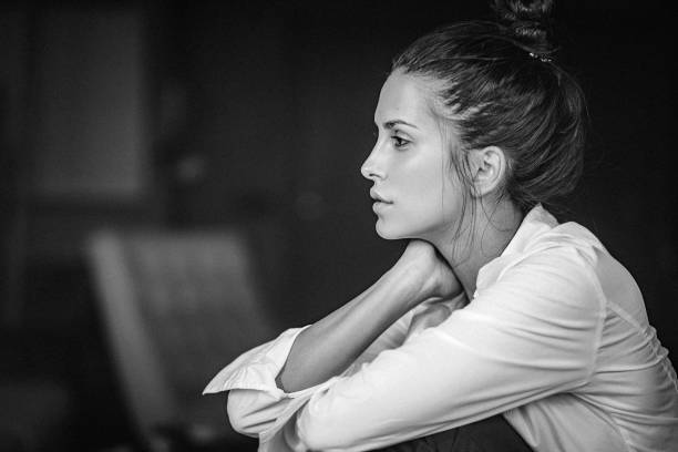 Black and white portrait of a pensive young woman in white shirt stock photo
