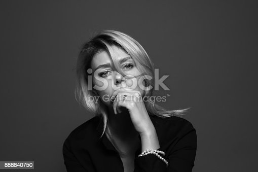 istock Black and white portrait of a sad young woman, looking to the camera, holding hands on her mouth. 888840750