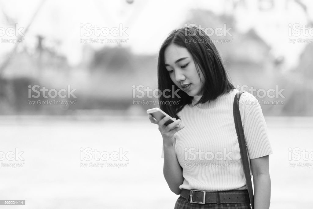 Black and white portrait of a young Asian woman in Bangkok downtown district, taking a break, texting on the cellphone zbiór zdjęć royalty-free