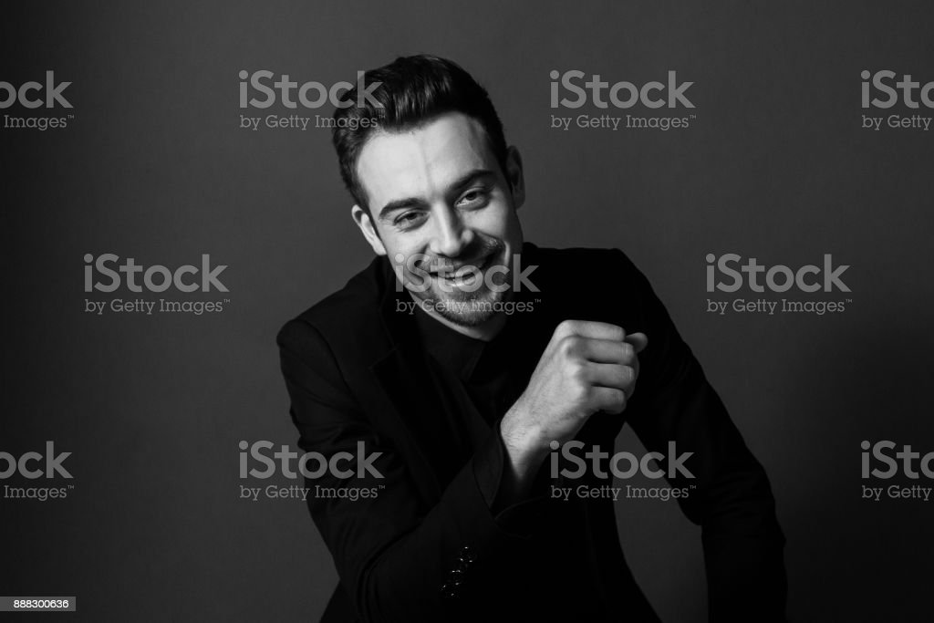 Black and white portrait of a young handsome man in a suit, smiling and looking at the camera stock photo