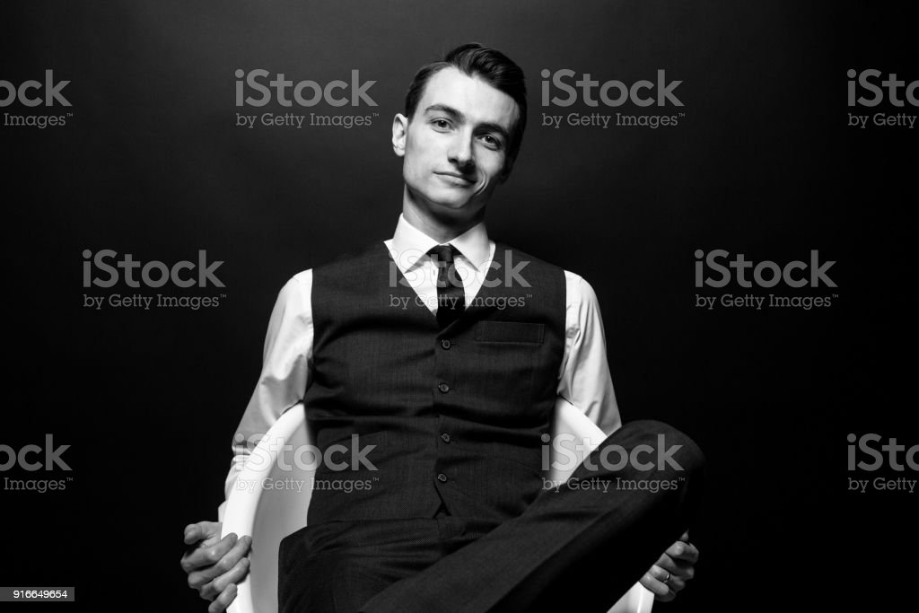 Black and white portrait of a young handsome man in a white shirt, black tie and vest, sitting and looking at the camera stock photo