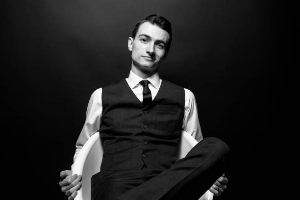 black and white portrait of a young handsome man in a white shirt, black tie and vest, sitting and looking at the camera - arrogance stock pictures, royalty-free photos & images