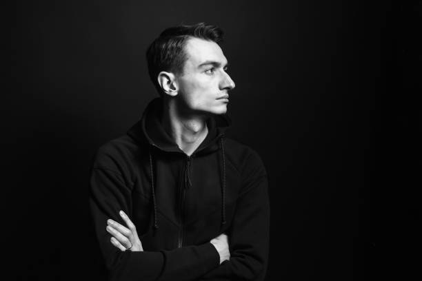 Black and white portrait of a young man in a black sweatshirt Black and white studio portrait of a young man in a black sweatshirt, arms crossed, seriously looking to the side, against plain studio background hood clothing stock pictures, royalty-free photos & images