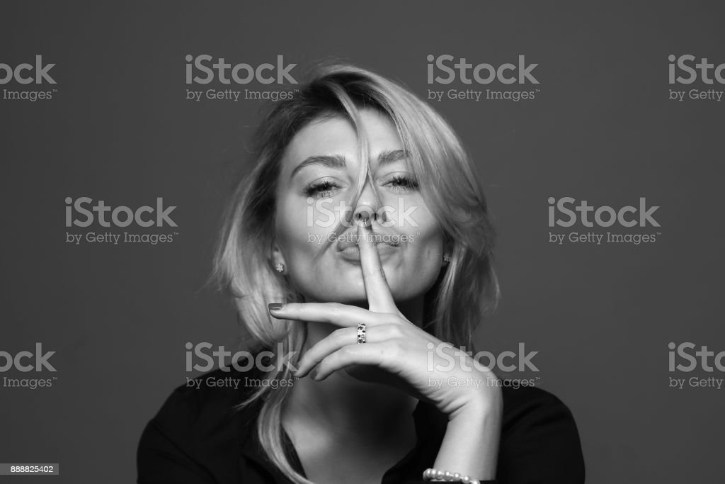 Black and white portrait of a young woman, holding a hand near face, finger on the lips. stock photo