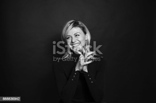 istock Black and white portrait of a young woman, laughing, looking to the side, holding hands together. 888836942