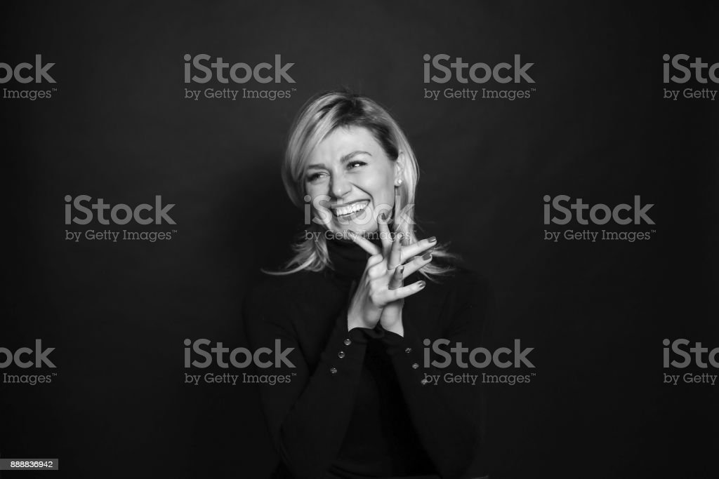 Black and white portrait of a young woman, laughing, looking to the side, holding hands together. stock photo