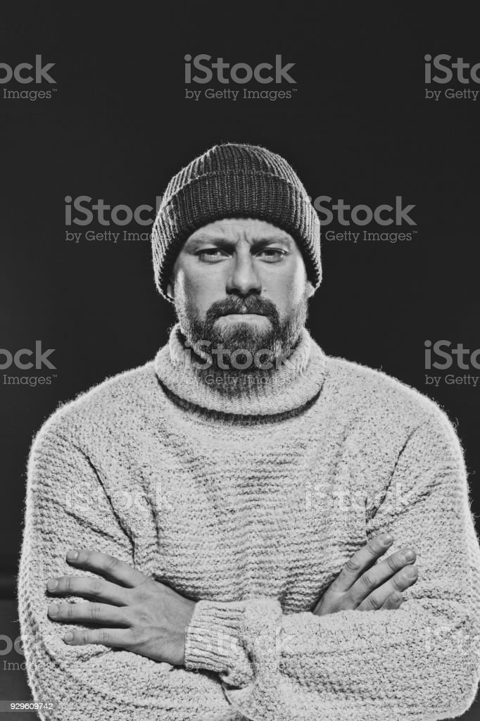 Black and white portrait of bearded, handsome man against dark background Monochrome portrait of bearded, handsome man wearing sweater and beanie hat, looking at camera. Studio shot, black background. 30-34 Years Stock Photo
