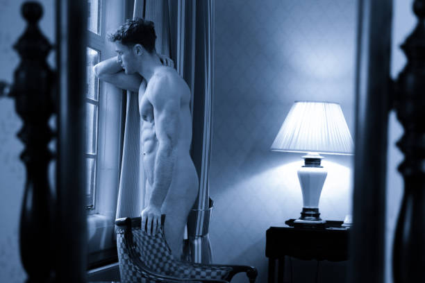 Black and white portrait of handsome naked man with muscular body standing by large window of hotel room stock photo