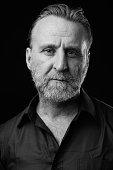 Studio Portrait Of Mature Man With Beard Against Black Background