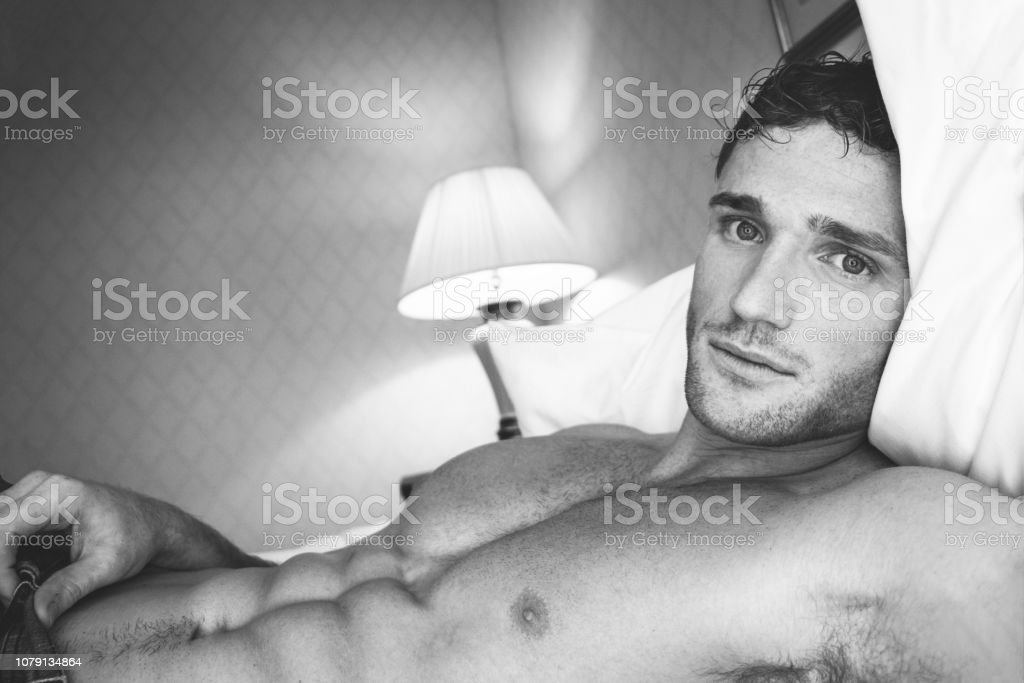 Black and white portrait of sexy shirtless man with pecs and six pack abs looking at camera stock photo