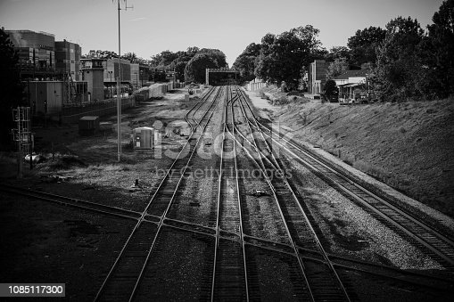 A black and white dramatic view of parallel railway tracks going toward a tree lined horizon.