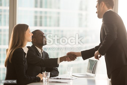 istock Black and white recruitment officers welcoming applicant arrived for interview 695760146