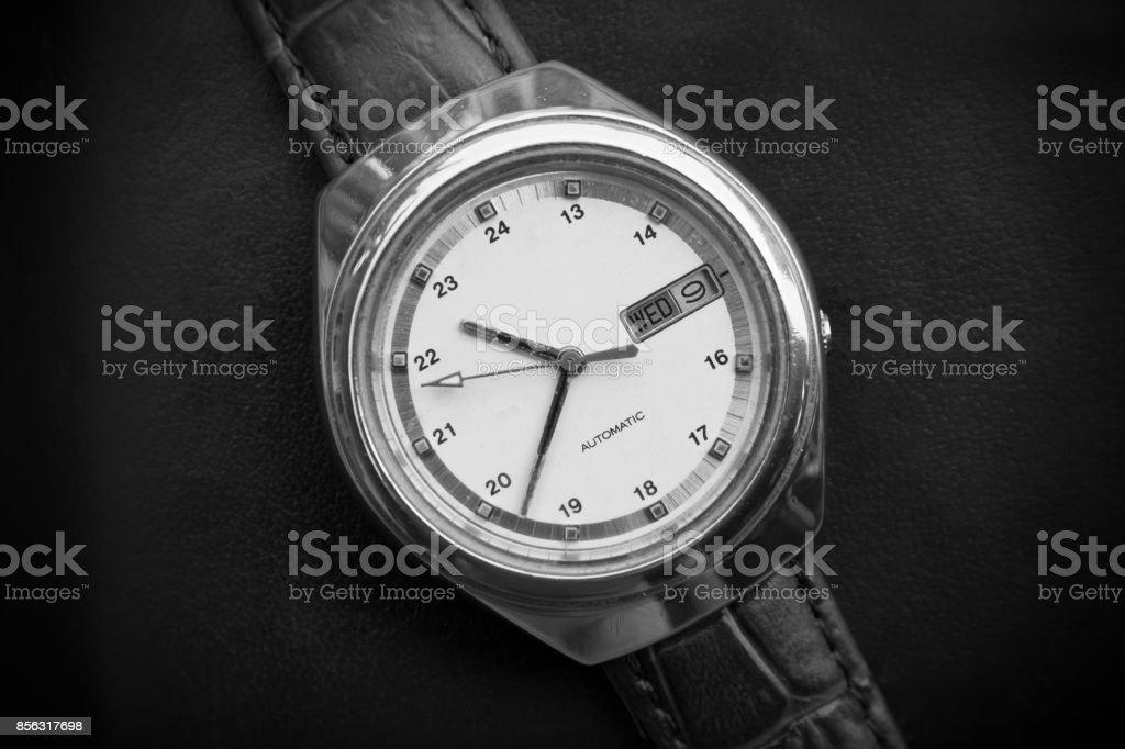 Black and white retro men wrist watch on black leather background.Old men wrist watch stock photo