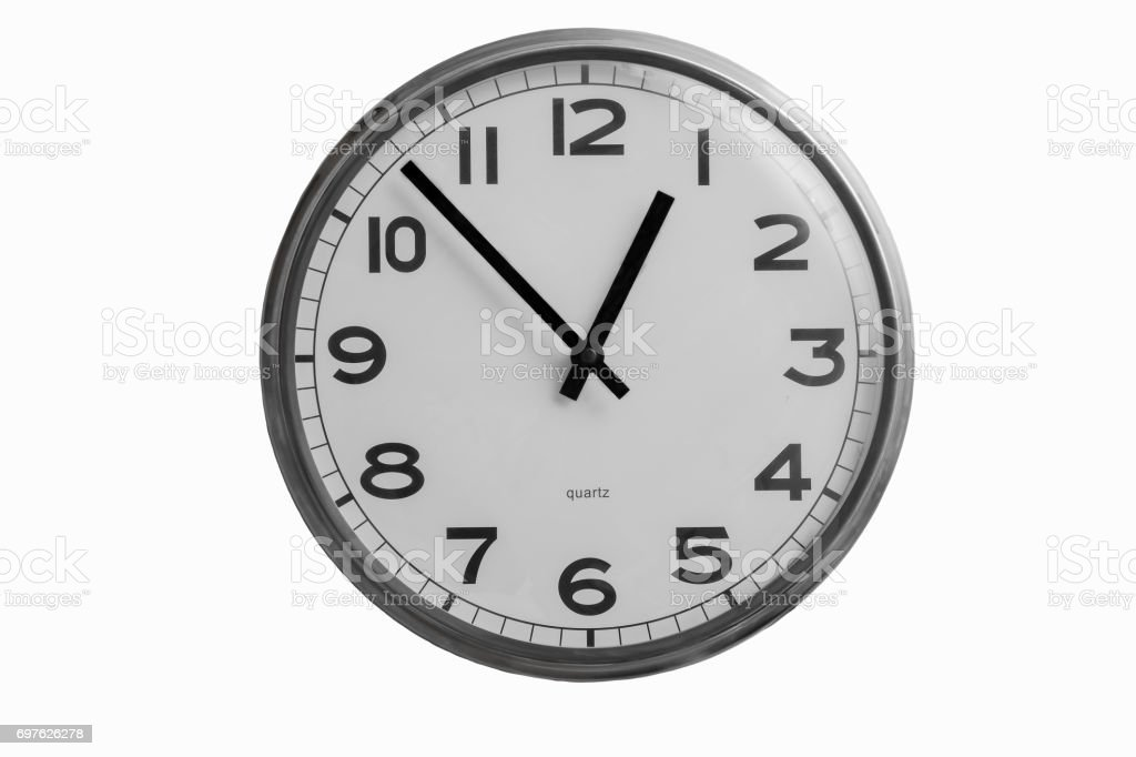 Black and white round wall clock shows almost one o'clock isolated on white background stock photo