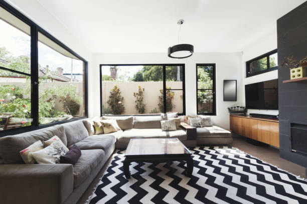 Black and white scheme living room with wood and grey tiling accents and chevron pattern floor rug stock photo