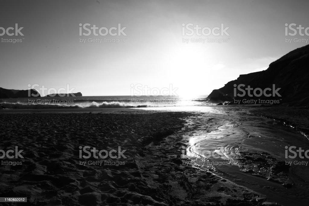 Black and white photo of sandy Cornish beach in the bright sunshine