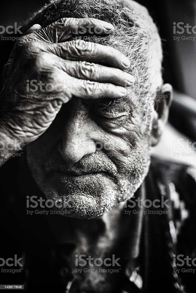 Black and white senior man touching his hand to his forehead royalty-free stock photo