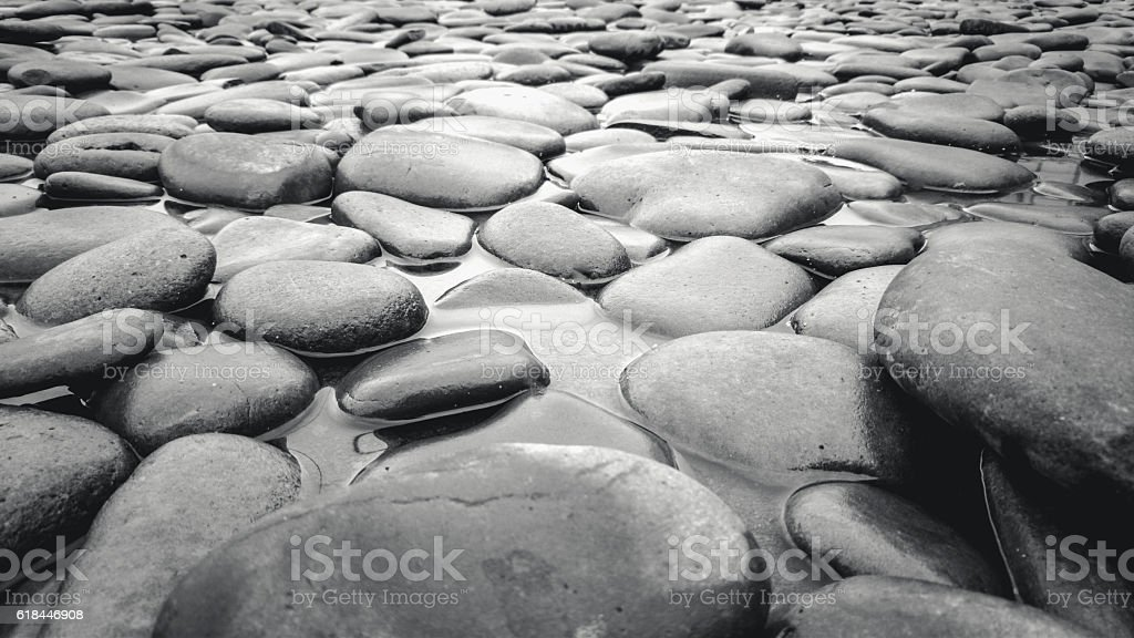 Black and white shot of river bed with pebbles stock photo