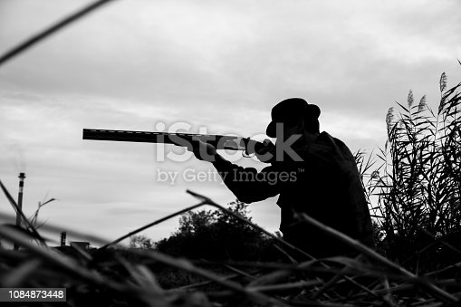 Black and white silhouette of Caucasian hunter wearing green suit and hat aiming on the pray on the field