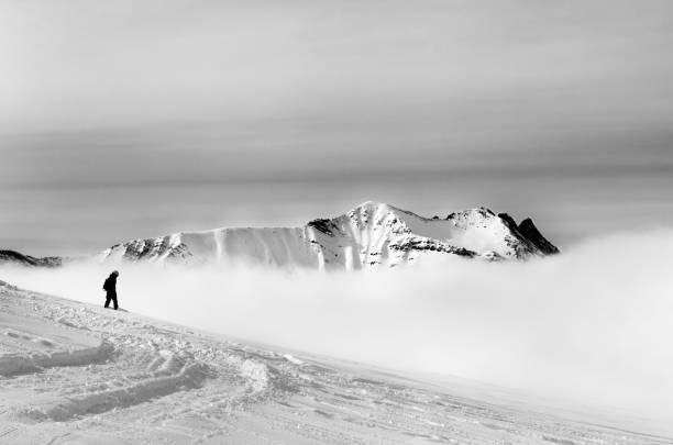 Black and white silhouette of snowboarder on off-piste slope with newly fallen snow and mountains in fog - foto stock