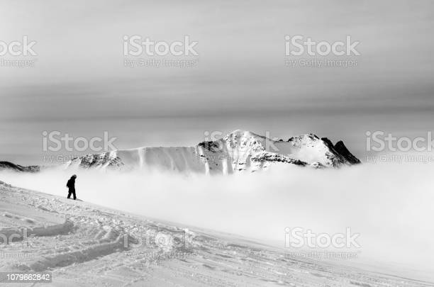 Photo of Black and white silhouette of snowboarder on off-piste slope with newly fallen snow and mountains in fog