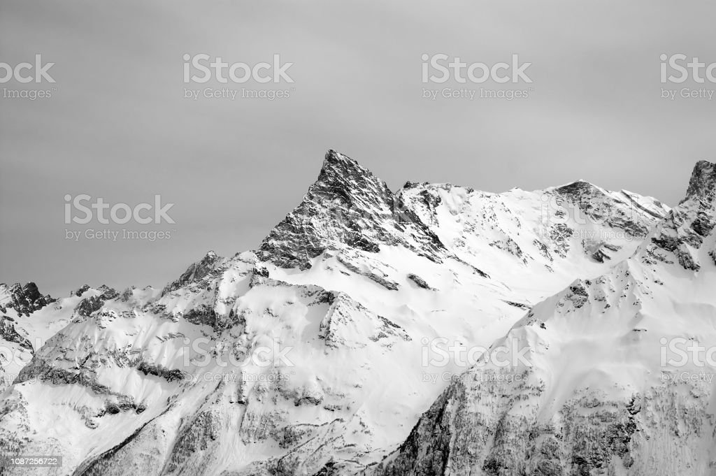 Black and white snowy mountains and grey cloudy sky. Caucasus...