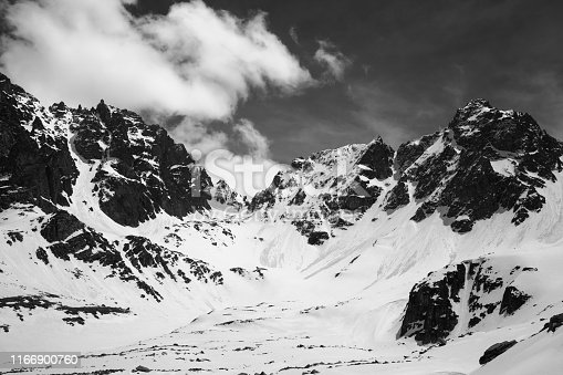 Snowy sunlit mountains with traces from avalanches and cloudy sky in sunny winter day. Turkey, Kachkar Mountains, highest part of Pontic Mountains. Black and white toned landscape.