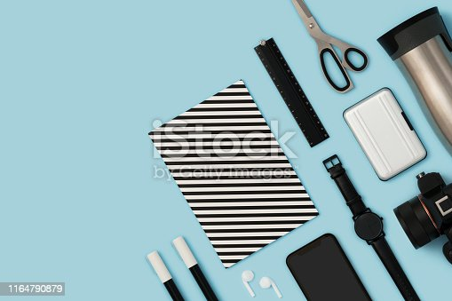 Back to school flat lays on blue background. Black and white stationary flat lay on blue background