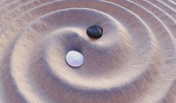 Black and white stones in sand. Yin-Yang symbol. 3D rendered illustration. stock photo