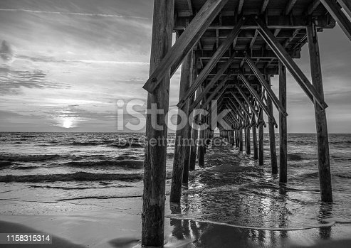 The pier in Surf City, NC in black and white at sunrise.