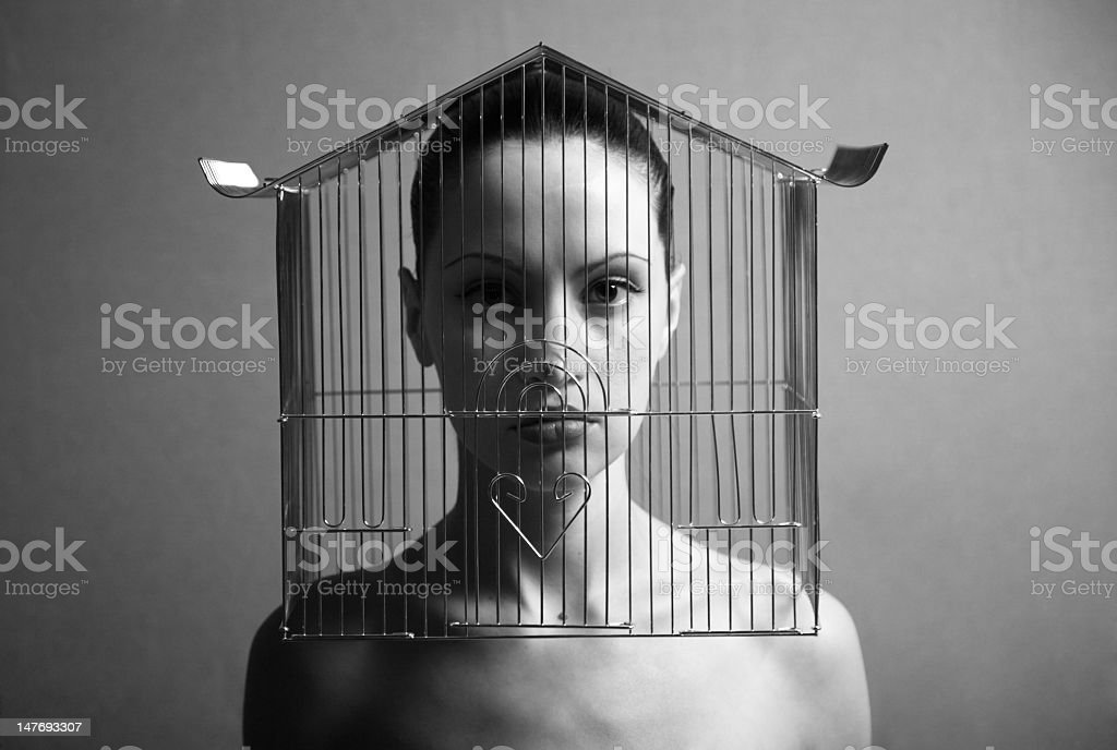 Black and white surreal image stern naked woman in birdcage stock photo