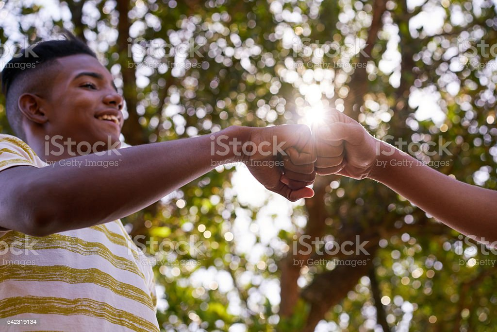 Black And White Teenagers Joining Hands Against Racism stock photo