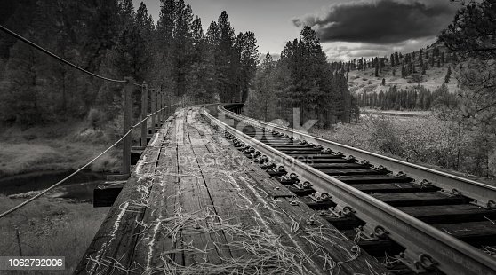 A black and white photo of train tracks running across the top of a trestle, running off into the distance